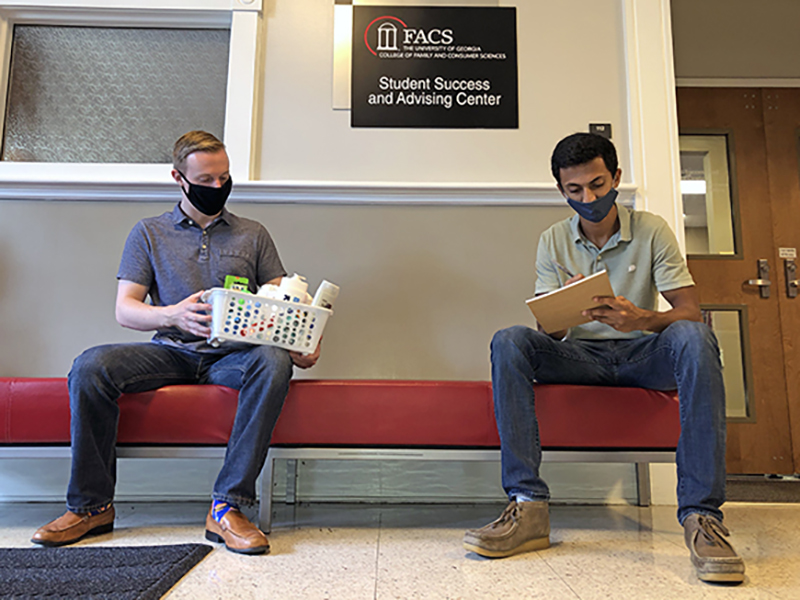 Terry College of Business MIS students Nick Loudermilk, left, and Nishant Sripathi work on improving the fulfillment process for nonprofit Bulldog Basics.