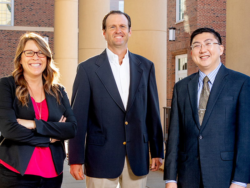 From left: Jessica Rodell, John Turner and Son Lam pose outside Amos Hall.
