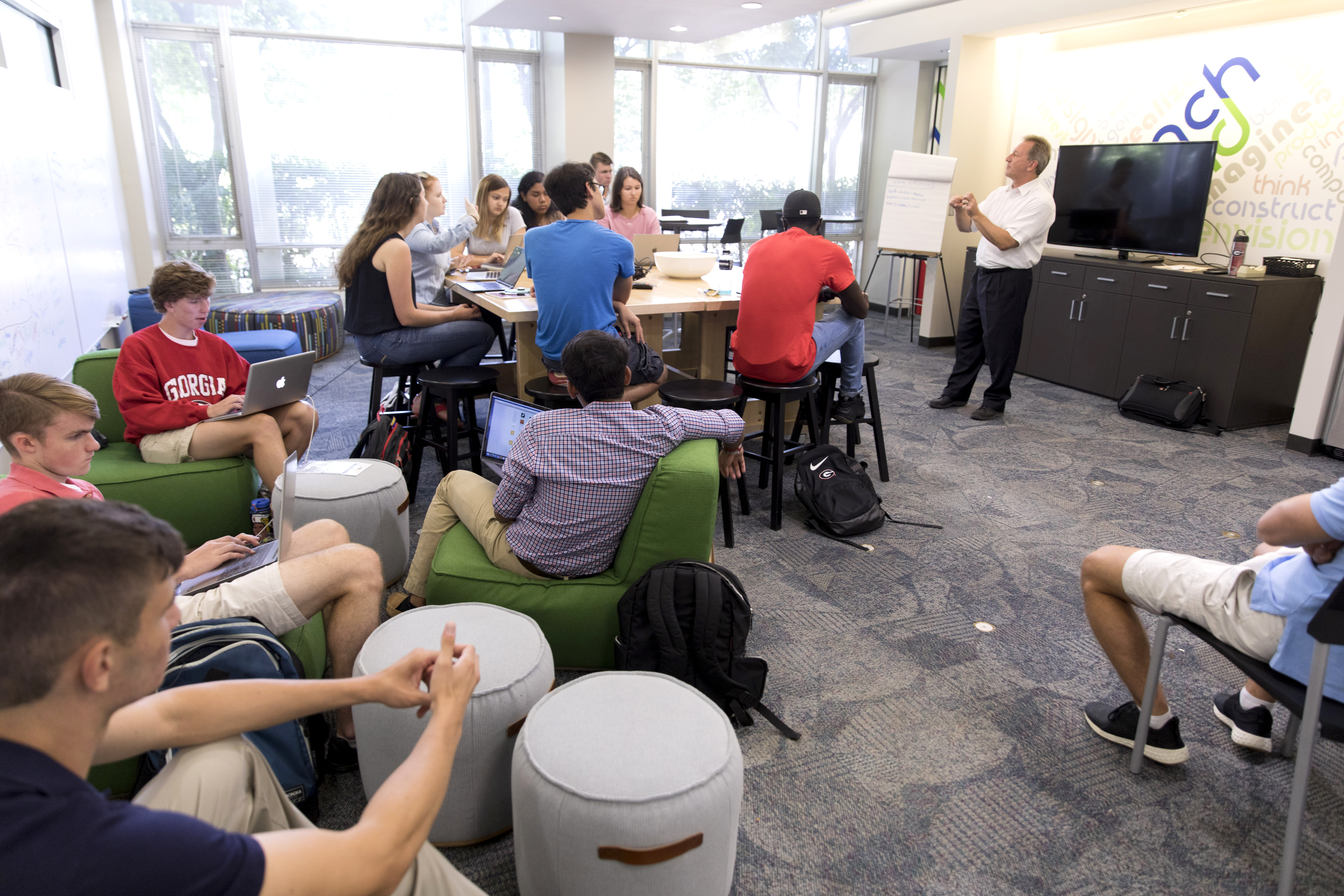 Donald Chambers, lecturer and associate director of the entrepreneurship program far right, talks with students during class