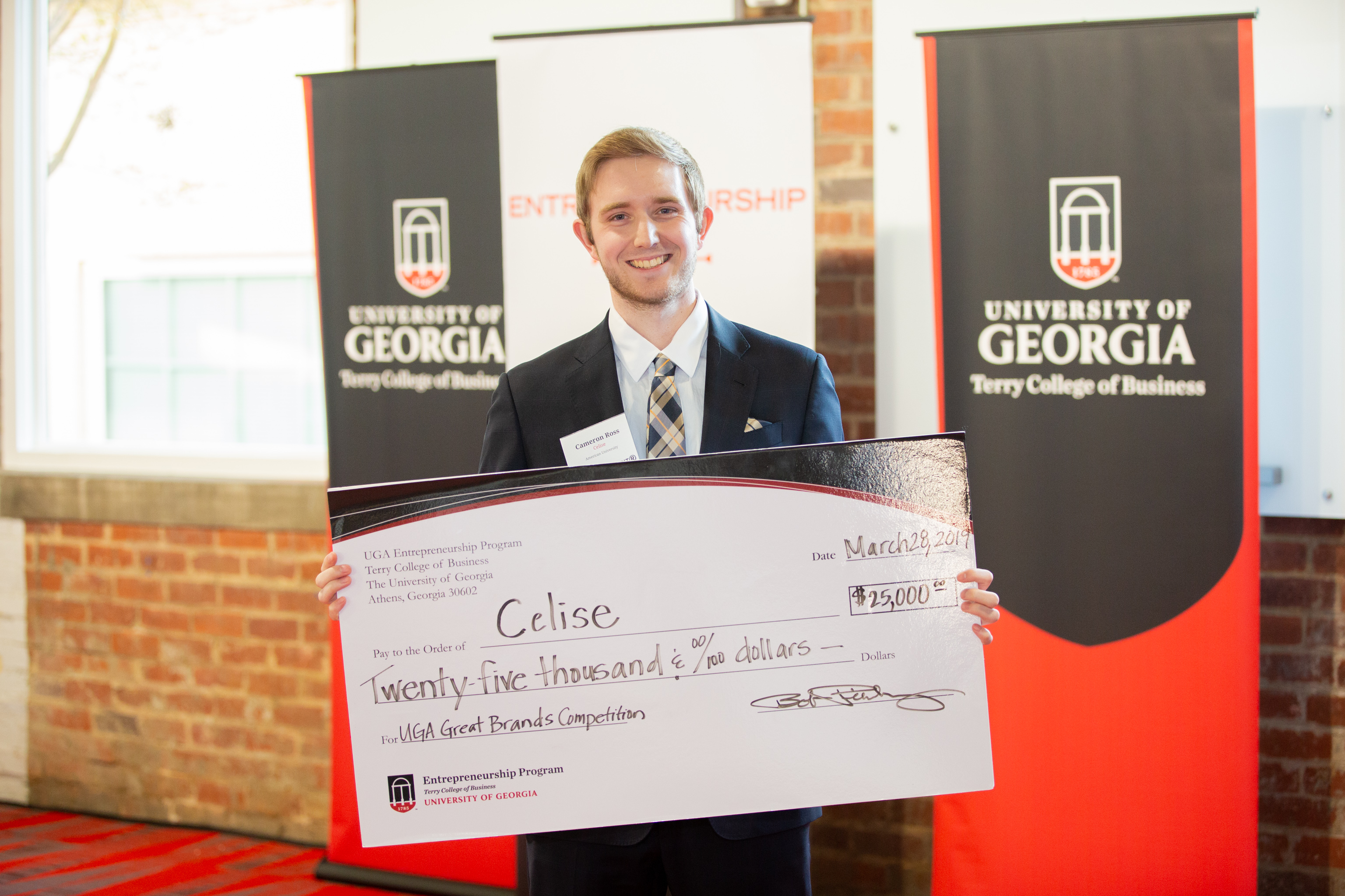 Cameron Ross, an American University student and founder of Celise, holds the first-place check for $25,000 at the Collegiate Great Brands Competition.