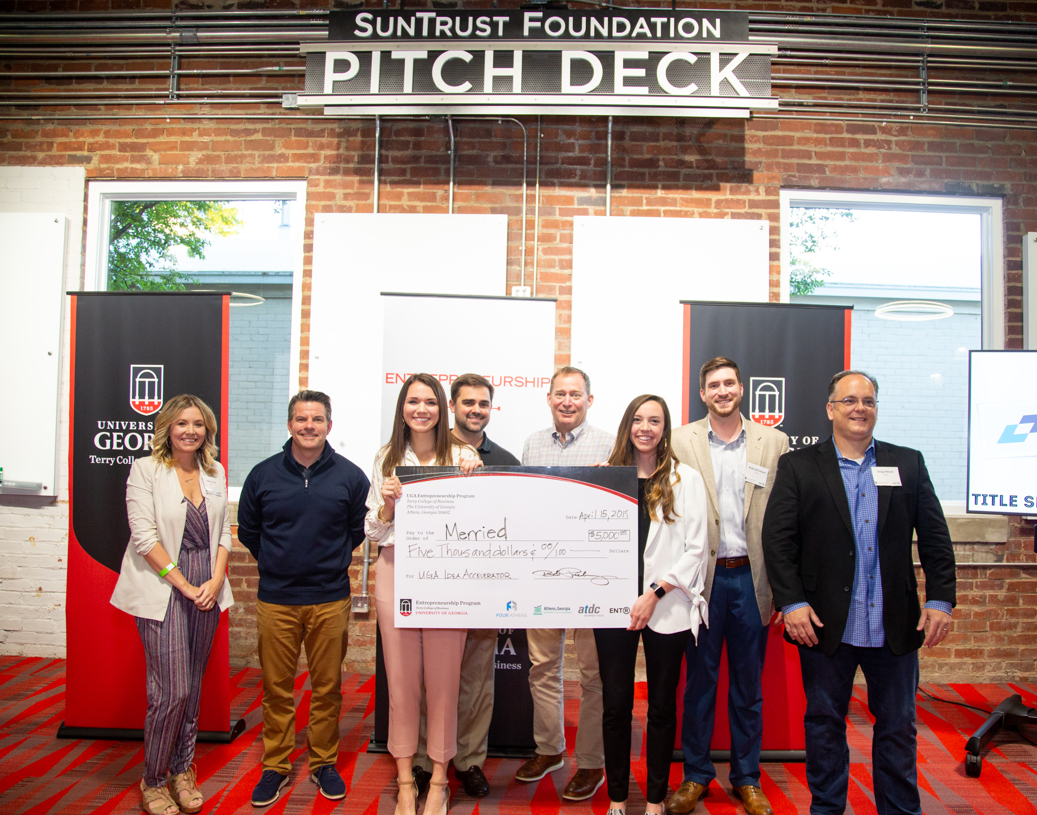 Merried app creators Megan Staebell and Emily Ruff pose with judges and their first-prize check at the Spring 2019 Idea Accelerator Demo Day.